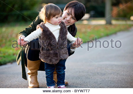 A mother helping her daughter stand in the park - Stockfoto