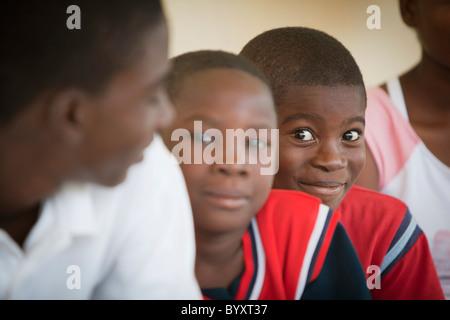 boys sitting in a row; grand saline, haiti - Stock Photo