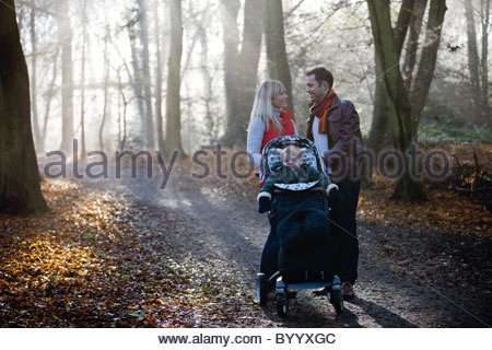 A young couple standing with a stroller in the park, talking - Stock Photo