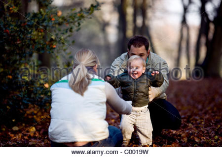 A young boy taking his first steps in the park - Stock Photo