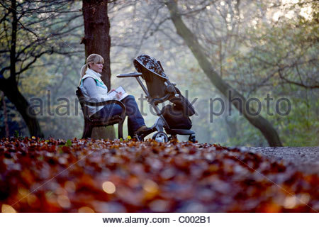 A young mother sitting on a bench, writing in a journal - Stock Photo