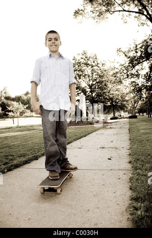 A young teenage boy standing on his skateboard in the park. Sepia tone. - Stock Photo