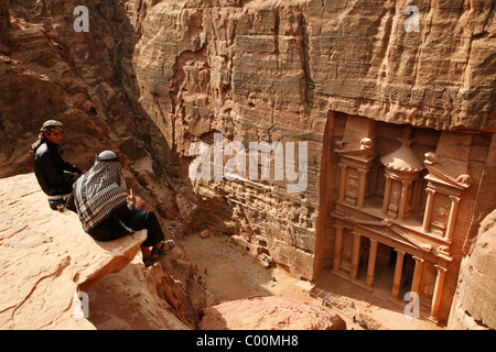 Bedouins sitting on top of a cliff looking down to the Treasury (El Khazneh), Petra, Jordan. - Stock Photo