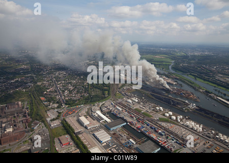 Aerial view, smoke, fire on a scrap island in the Duisport inland port, Duisburg, Ruhrgebiet region, North Rhine - Stock Photo
