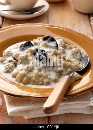 Individual portion of porridge and fruit vegetarian breakfast - Stock Photo