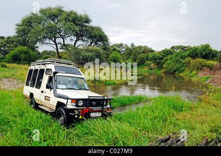 Toyota Land Cruiser off-road vehicle crossing the Khwai River on an old wooden bridge near the Okavango Delta, Botswana, - Stock Photo