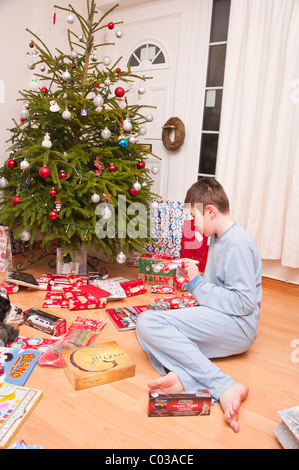 A MODEL RELEASED picture of an eleven year old boy opening christmas presents under the tree in the Uk - Stock Photo