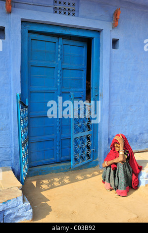 Elderly Indian woman wearing a red sari sitting on the floor in front of a blue-painted door, Thar Desert, Rajasthan, - Stockfoto