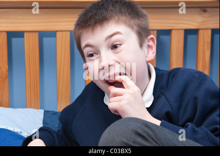A MODEL RELEASED picture of an eleven year old boy picking his wobbly tooth in his bedroom in the Uk - Stock Photo