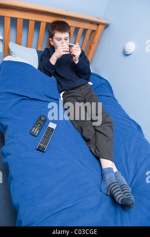 A MODEL RELEASED picture of an eleven year old boy playing with his ipod touch in his bedroom in the Uk - Stock Photo