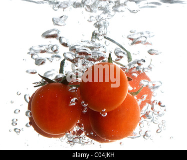 Some red round tomatoes in the water - Stock Photo