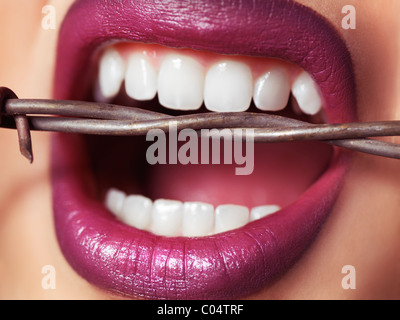Closeup of woman's mouth with strong healthy teeth biting into barbed wire - Stock Photo