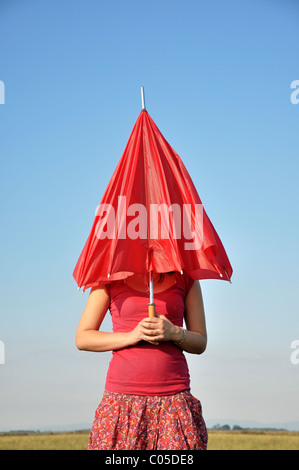 Young woman holding red umbrella - Stock Photo