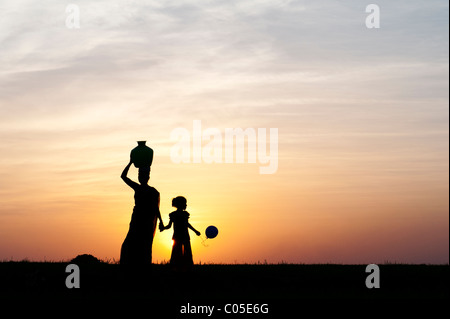 Indian mother carrying water pot holding childs hand with balloon in the indian countryside. Silhouette - Stock Photo
