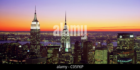 New York City skyline looking West with the Empire State Building and Chrysler Building at dusk. - Stock Photo