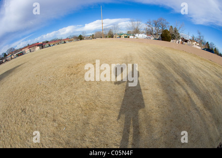 Shadow of a woman holding a heart shaped balloon, taking a picture under blue sky, fish eye lens. - Stockfoto