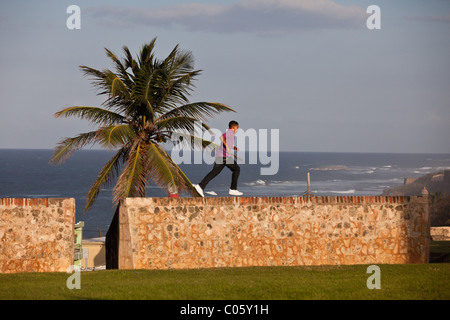 A young boy run along the old fortress wall of San Juan, Puerto Rico. - Stock Photo