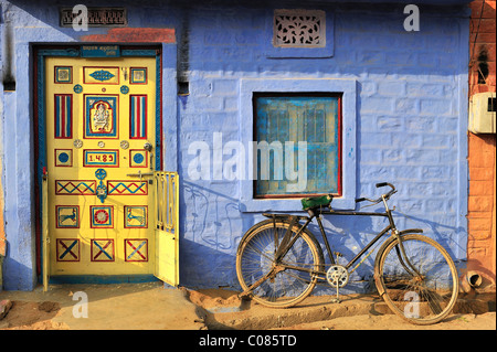Front door decorated with ornaments and a bicycle in front of a blue wall in an Indian village, Thar Desert, Rajasthan, - Stock Photo