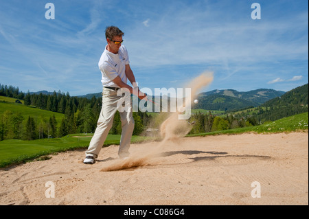 Golf player standing in the bunker batting the golf ball out of the sand, on alpine golf course, Achenkirch, Tyrol, - Stock Photo