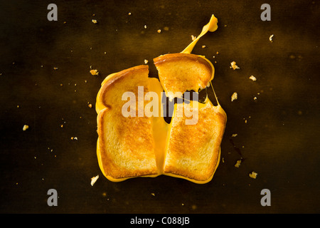 A Grilled Cheese Sandwich cut in half and with the top right corner broken off pulling the cheese on a wood table - Stockfoto