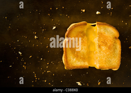 A Grilled Cheese Sandwich cut in half pulling the cheese on a wood table - Stockfoto