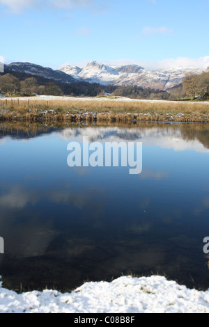 River Brathay at Elter water and view of snow on Langdale Pikes - Stockfoto