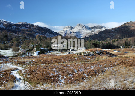 Village of Elter water and view of snow on Langdale Pikes - Stockfoto