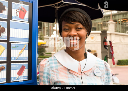 Young African American woman greets ice cream customers with a smile at Disney World's Magic Kingdom in Orlando, - Stock Photo