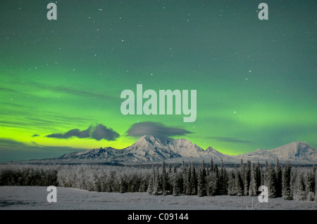 Green Aurora Borealis lights up the night sky above Mt. Sanford and Mt. Drum in the Wrangell Mountains near Kenny - Stock Photo