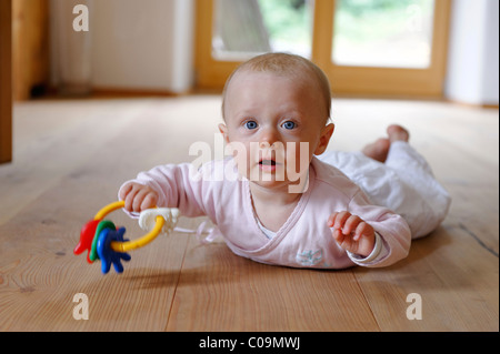 Small baby, 4 months, lying on her belly, with teether - Stock Photo