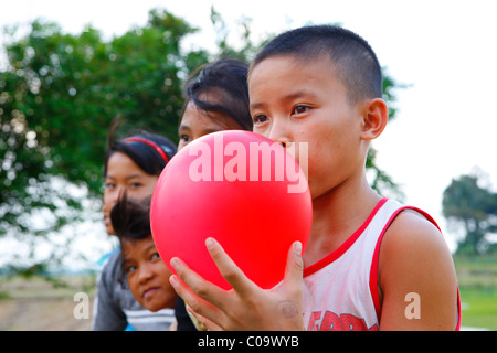 Boy blowing up a red balloon, Margaritha children's home, Marihat, Batak region, Sumatra island, Indonesia, Asia - Stock Photo