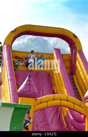 Children playing on inflatable slide and bouncy castle - Stock Photo
