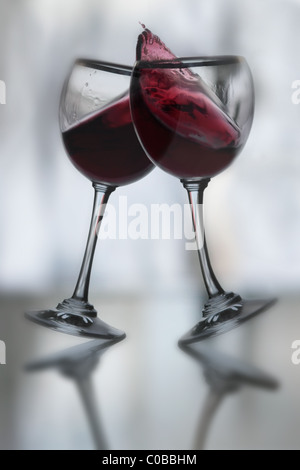 dancing red wine glasses tilted in a toast to each other with dynamic movement,  wine spilling over,  curved stem - Stockfoto