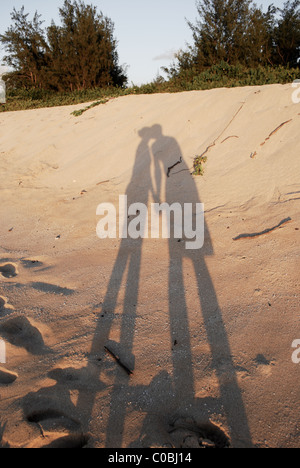 Shadow of couple kissing on beach. Holding hands and kissing just before sunset. - Stock Photo