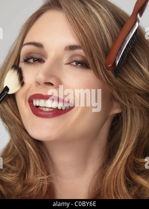 Portrait of a beautiful smiling young woman with her hair and makeup being done - Stock Photo