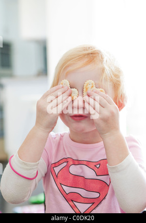 Little girl with crackers on her eyes - Stock Photo