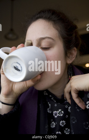Young woman downs a cup of coffee at a cafe in Brooklyn, NY. - Stock Photo