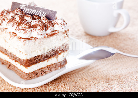 Portion of tiramisu dessert served on a white shaped plate and a cup of coffee - Stock Photo