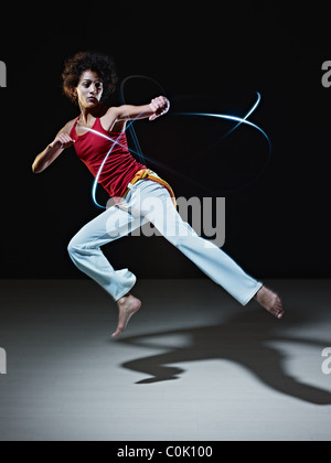 young adult latin american female doing capoeira flying kick in gym, with streaks of led lights all around. - Stockfoto