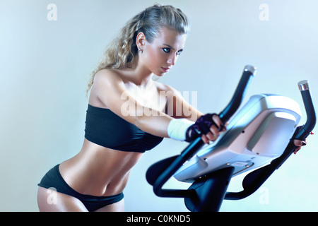 Young woman on exercise bicycle. Soft blue tint. - Stockfoto