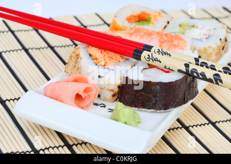 Mixed sushi on a plate with wasabl, ginger and chopsticks - Stock Photo
