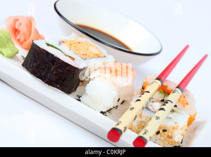 Mixed sushi on a plate with a bowl of soy suce and chopsticks - Stock Photo