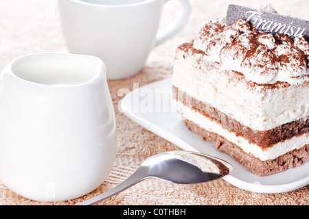 Portion of tiramisu dessert served on a white shaped plate and a cup of coffee with cream - Stock Photo