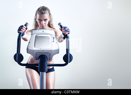 Young woman on exercise bicycle on wall background. - Stockfoto