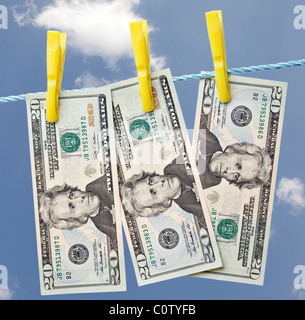 a row of twenty dollar bills pegged out on a washing line against a blue sky with white clouds - Stock Photo