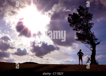 Bicycle rider stand on the hill watching the sunlight and relax - Stock Photo