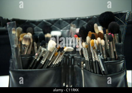 Make up artists are equipped with an arsenal of make-up brushes backstage before the presentation of Mr. Start autumn - Stock Photo