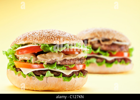 Two hamburgers on yellow background. - Stock Photo