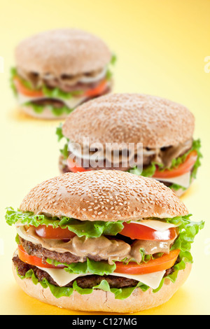 Three delicious hamburger on a yellow background - Stock Photo
