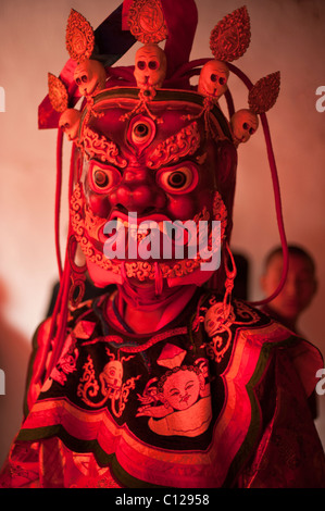 Buddhist monk dressed in ritual dance costume representing a god or demon prepares to dance at a religious festival - Stock Photo
